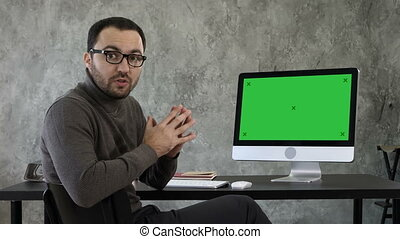 Portrait of handsome young man in casual in the office talking to the camera explaining something near the screen. Green Screen Mock-up Display.