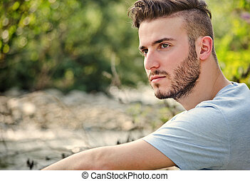 Portrait of handsome young man in white t-shirt in nature