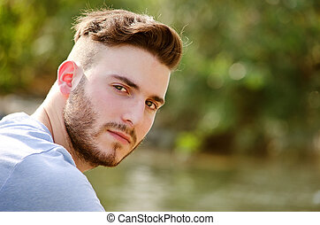 Portrait of handsome young man outdoors in nature