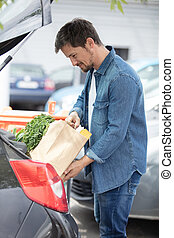 portrait of handsome young man packing groceries into car trunk