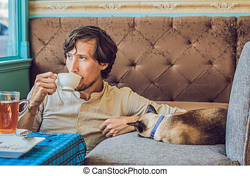 Portrait of handsome young man playing with cat and drinks coffee