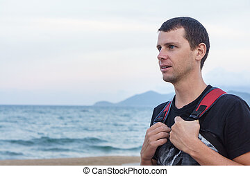 portrait of handsome young man standing against a beach