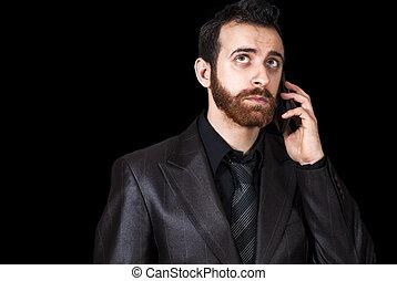 man talking on mobile against a black background
