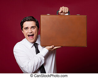 portrait of handsome young man with case on the wonderful burgundy studio background