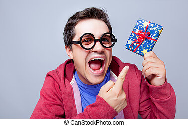 portrait of handsome young man with cute gift on the wonderful grey studio background