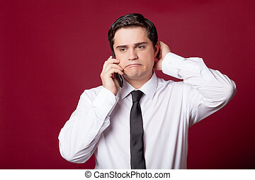 portrait of handsome young man with phone on the wonderful burgundy studio background