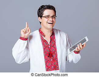 portrait of handsome young man with tablet on the wonderful grey studio background