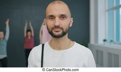 Portrait of handsome young man with yoga mat smiling looking at camera in studio