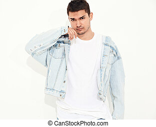 Portrait of handsome young model man dressed in jeans clothes posing on white background. Isolated