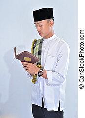 Portrait of handsome young muslim man enjoy reading (tilawat...