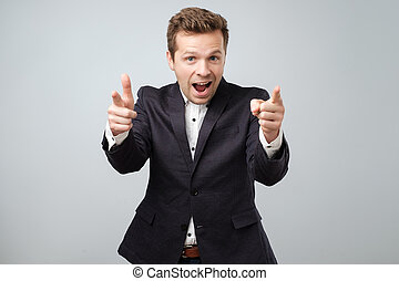 Portrait of handsome young smiling man pointing fingers at camera, picking you as winner
