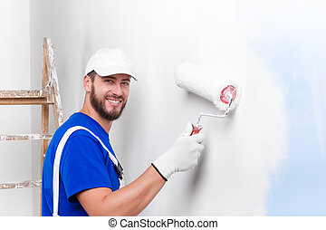 Portrait of handsome young smiling painter in white dungarees, blue t-shirt, cap and gloves painting a wall with paint roller, looking at camera