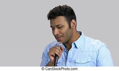Portrait of handsone dark-skinned man performing song with microphone.