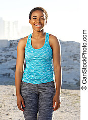 happy african american fitness woman standing outside