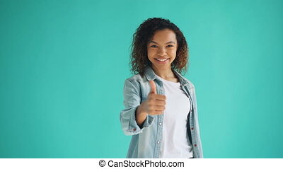 Portrait of happy African American girl showing thumbs-up...