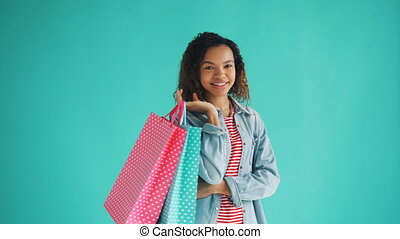 Portrait of happy African American girl with shopping bags...