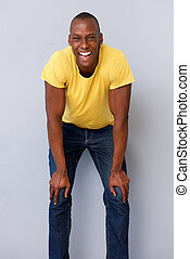 happy african american man laughing with hands on knees