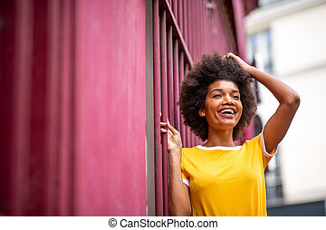 happy african American woman laughing outside with hand in hair