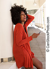 happy african american woman leaning on wall with mobile phone