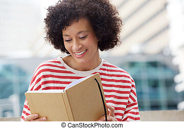 happy african american woman reading from book