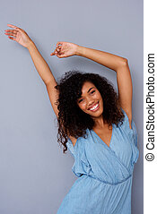 happy african american woman smiling with arms raised