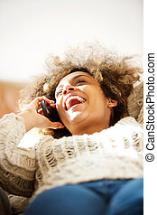happy african american woman talking on cellphone and laughing