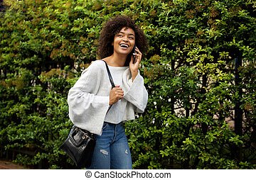 happy african american woman talking with cellphone by trees