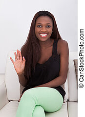 African American woman waving while sitting on sofa