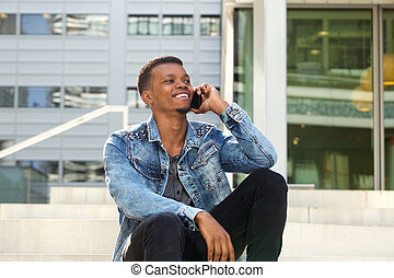 happy african man sitting outside on phone call