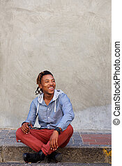 happy african man sitting outside on sidewalk