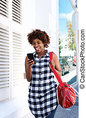 happy african woman walking in the city with cellphone and bag