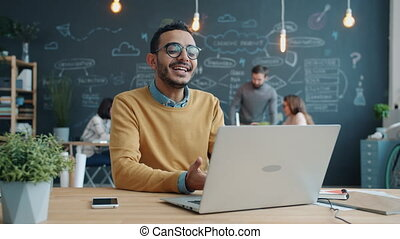 Portrait of happy Afro-American businessman making video call using laptop at work