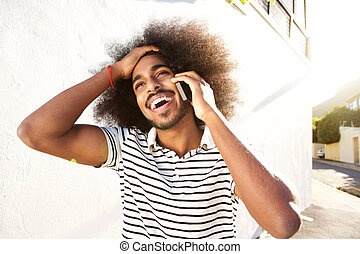 happy afro man on telephone call walking outside