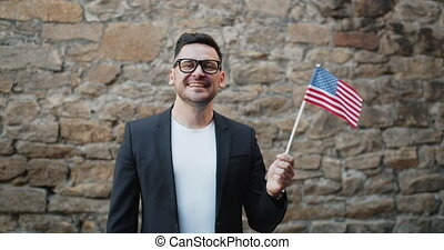 Portrait of happy American man waving official US flag...
