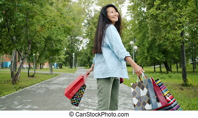 Portrait of happy Asian girl shopaholic spinning in green park holding shopping bags having fun alone. Joyful people, consumerism and lifestyle concept.