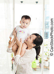 Portrait of happy asian mother and baby having fun together at home in white room, near window