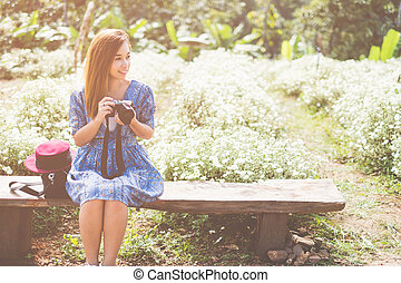 Portrait of Happy Asian woman holding camera  in The Chrysanthemum garden