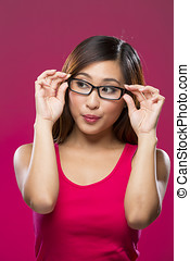 Portrait of Asian Woman looking away. Young fresh Chinese female model on bright pink background.