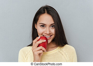 Portrait of happy attractive young woman with red apple