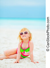 Portrait of happy baby girl in sunglasses sitting on beach
