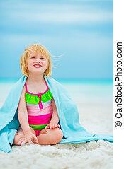 Portrait of happy baby girl in towel sitting on beach