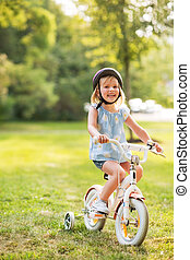 Portrait of happy baby girl riding bicycle outdoors in park