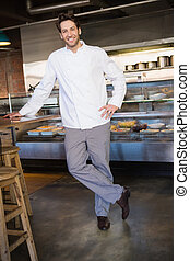 Portrait of happy baker leaning on counter