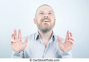 Portrait of happy bearded man with raised hands on light background