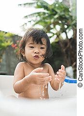 happy beautiful baby girl take a bath in a baby bath tube
