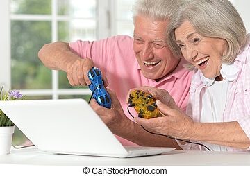 Portrait of happy beautiful senior couple playing computer game