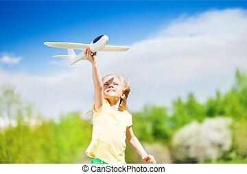 Portrait of happy blond girl holding airplane toy