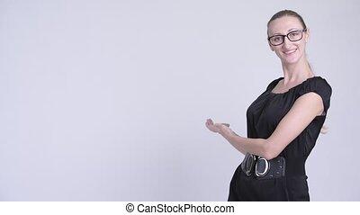 Portrait of happy blonde businesswoman showing something