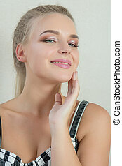 Portrait of happy blonde girl with natural makeup posing at white background