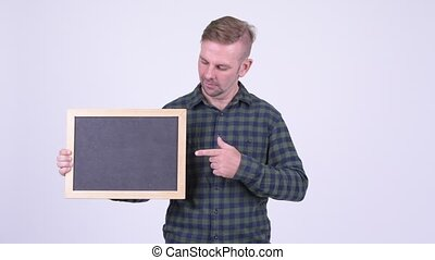 Portrait of happy blonde hipster man holding blackboard and giving thumbs up